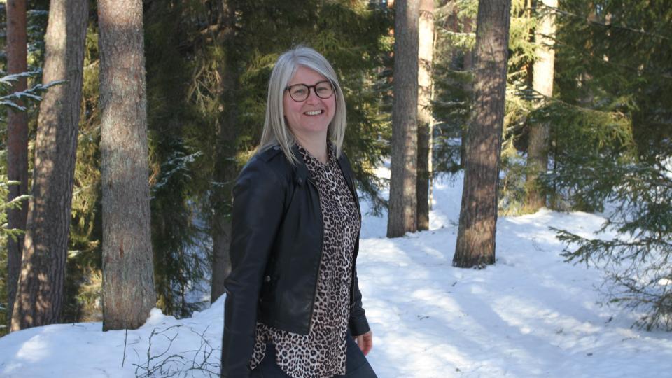 Nainen seisoo lumisen metsän edustalla