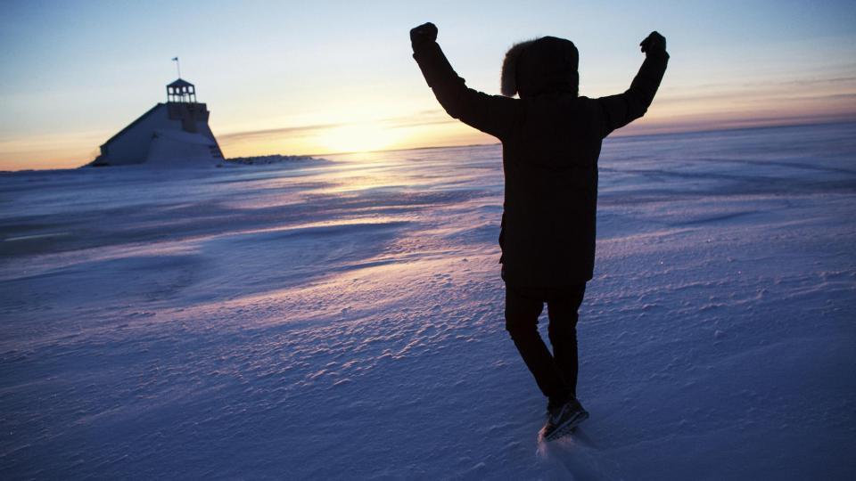 Mies tuulettaa meren jäällä
