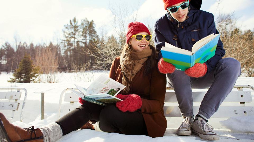 Kaksi nuorta lukemassa kirjoja aurinkolasit päässä puiston penkillä kevättalvella.