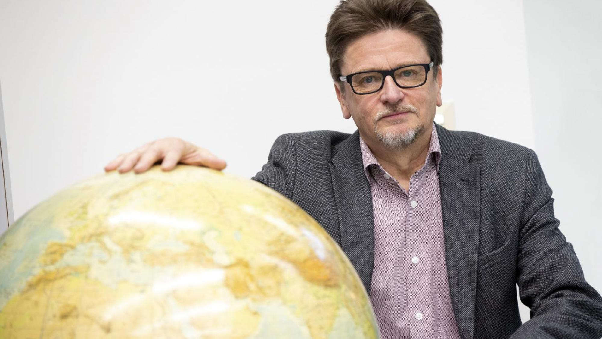 Professor Anssi Paasi hold his hand over a small scale model of Earth.
