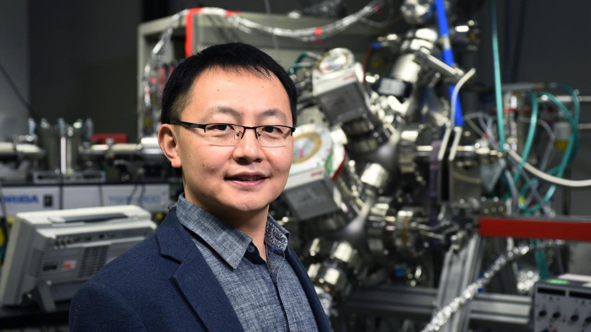 Associate Professor Wei Cao standing in front of lab equipment