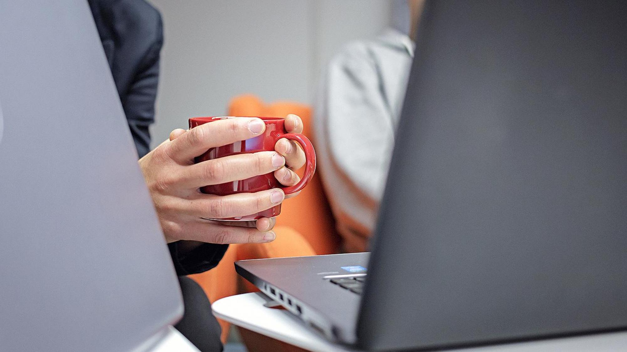The hands holding a coffee cup appear behind a laptop