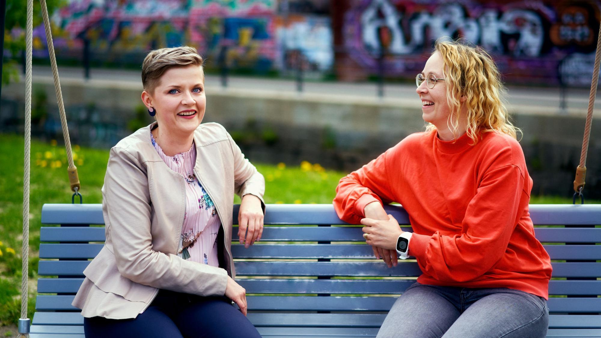 Kaksi naispuolista Oulun yliopiston alumnia istuu Ainolan puistossa kiikussa.