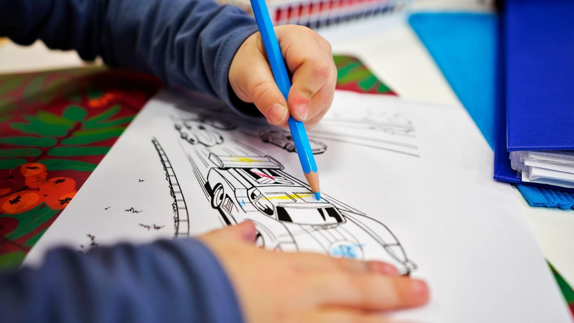 Päiväkoti-ikäinen lapsi värittää auton kuvaa sinisellä värikynällä; lähikuva lapsen käsistä ja värityskuvasta.