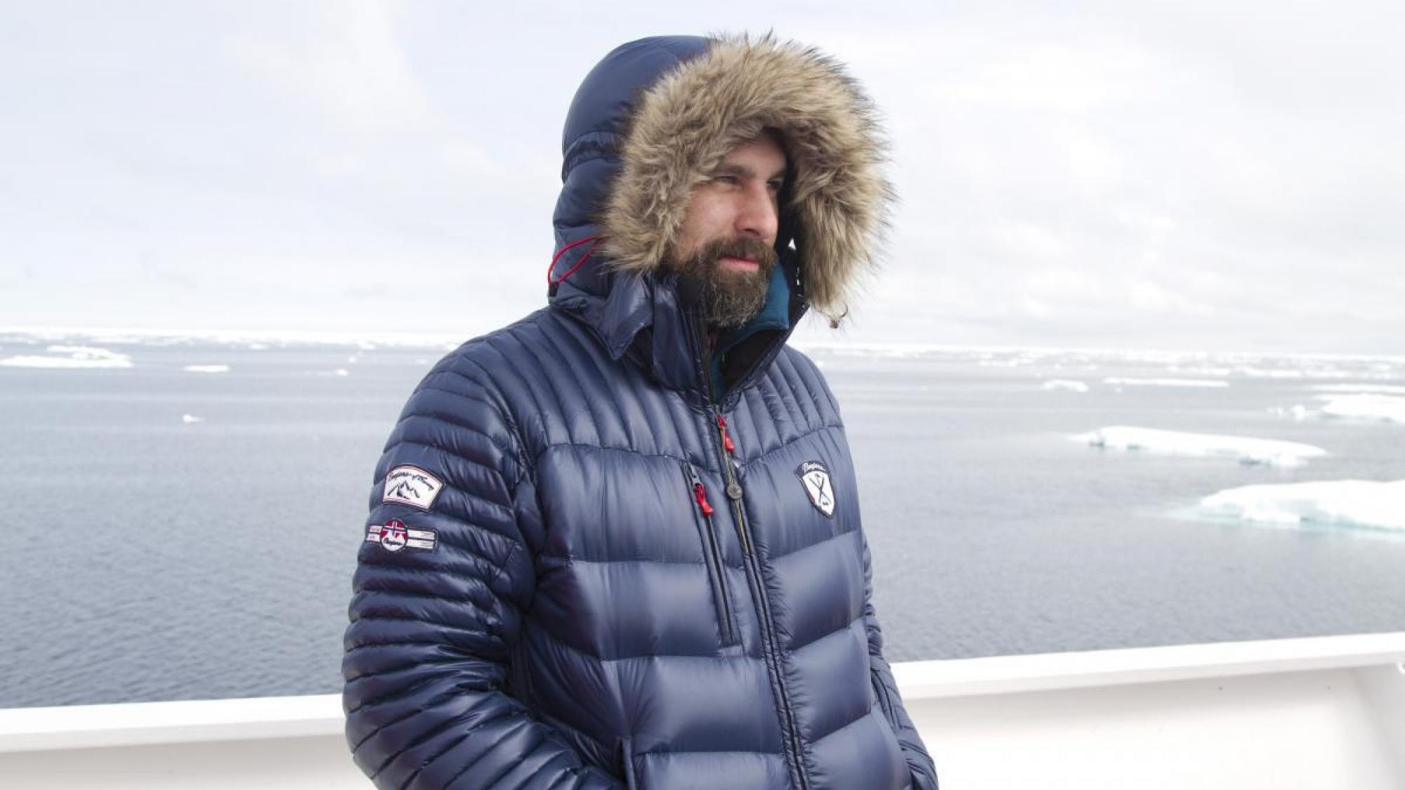 Roger Norum wearing hooded winter coat in arctic environment.