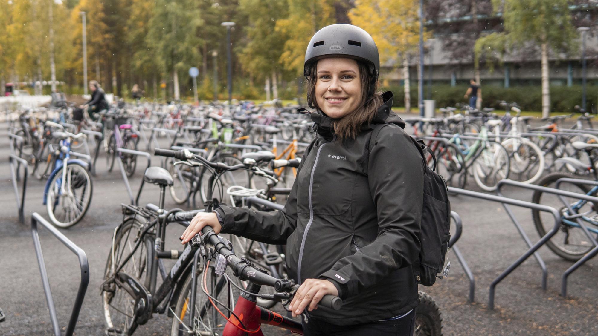 Nainen pyörän kanssa pyöräparkin edessä.