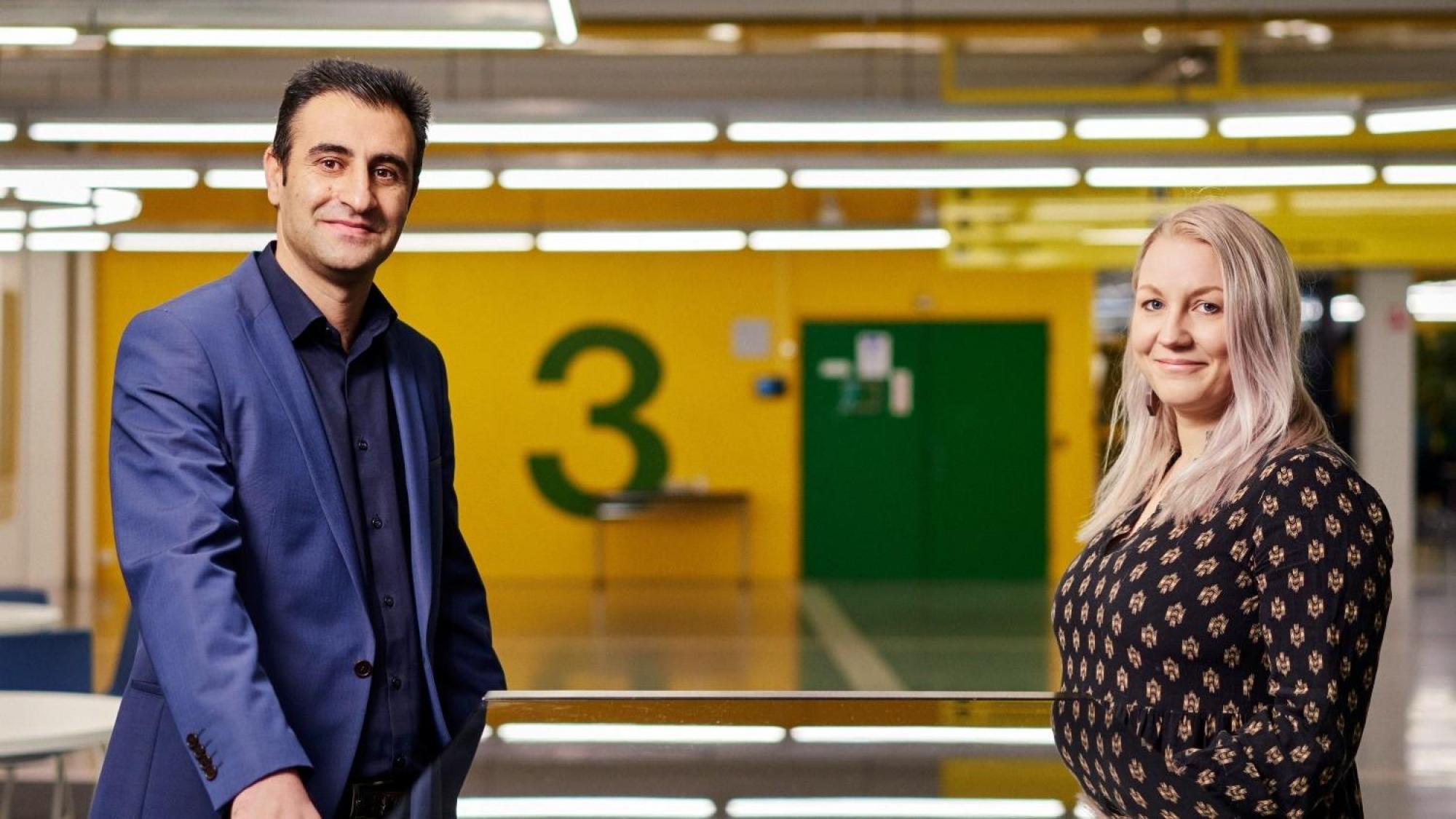 Siamak Seyfi and Noora Hirvonen standing in the University hallway.