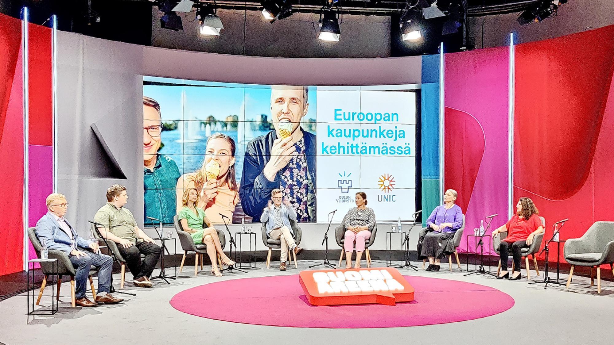 Panelistit Tapio Koivu, Eetu Leinonen, Tytti Tuppurainen, Mirja Vehkaperä ja Luz Peltoniemi sekä juontaja Janne Hopsu istumassa puoliympyrässä SuomiAreenalla.