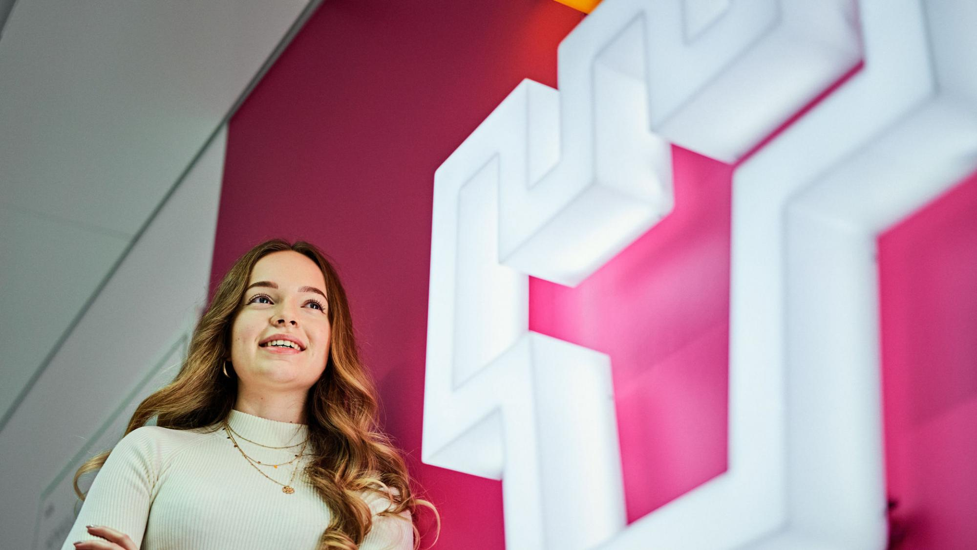 A young woman leans on a pink-coloured wall with a big illuminated logo of the University of Oulu attached to it.