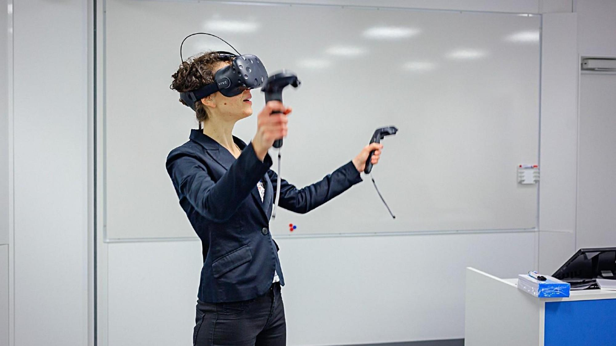 Woman wearing VR glasses and holding VR controllers in both hands.