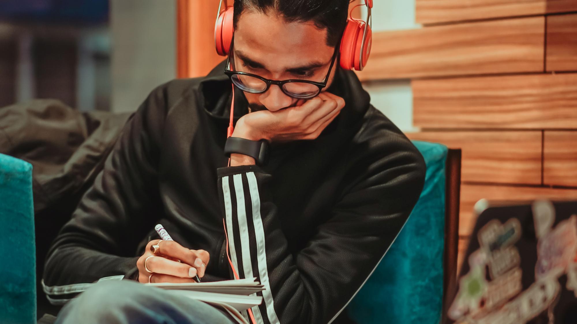 Nuori mies opiskelee kuulokkeet päässä